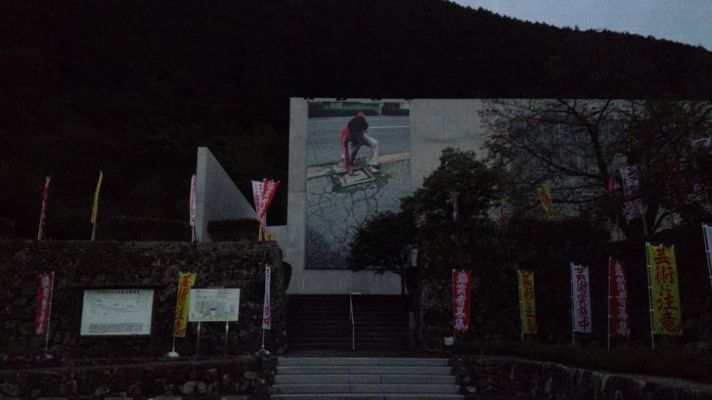 夕方の美術館。「田中偉一郎の芸術はノー・ビジョン」作品の写真が貼られています。